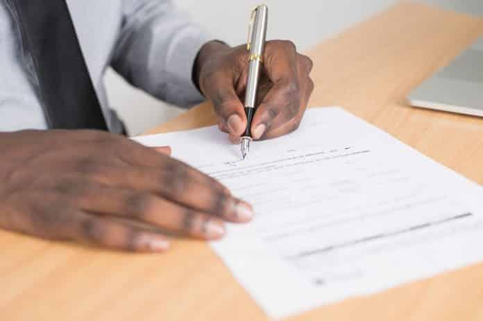 Un homme qui signe un document